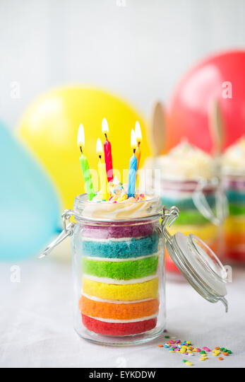 Rainbow layer cake in a jar with birthday candles - Stock Image