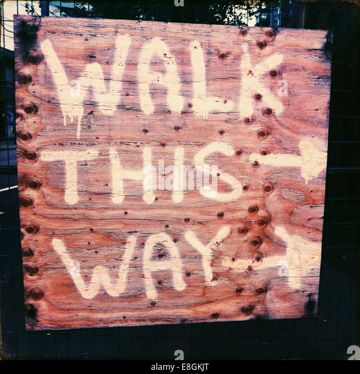 Walk this way Direction sign on sidewalk near construction site - Stock-Bilder