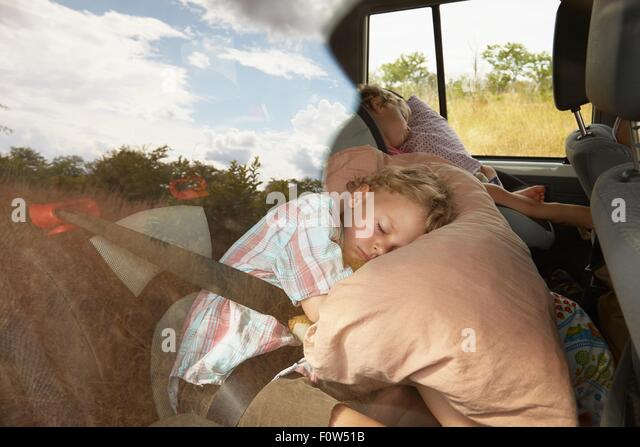 Two young boys asleep in back of off road vehicle - Stock Image