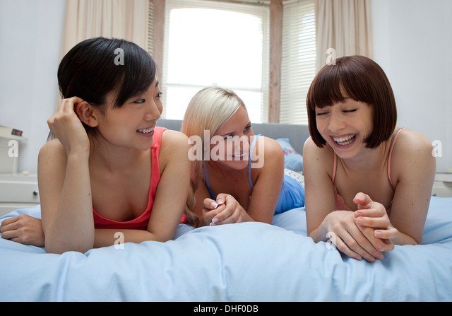 Group of young females on bed laughing - Stock Image
