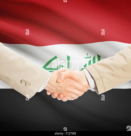 Businessmen shaking hands with flag on background - Iraq - Stock Image