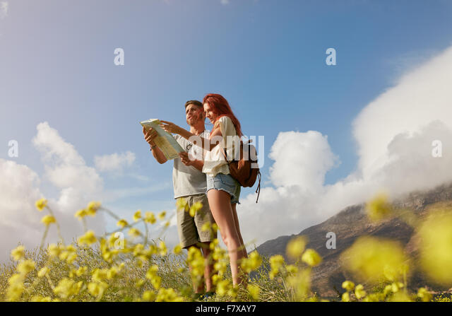 Young couple looking at map while standing outdoors in countryside. Hiking couple navigating together. - Stock-Bilder
