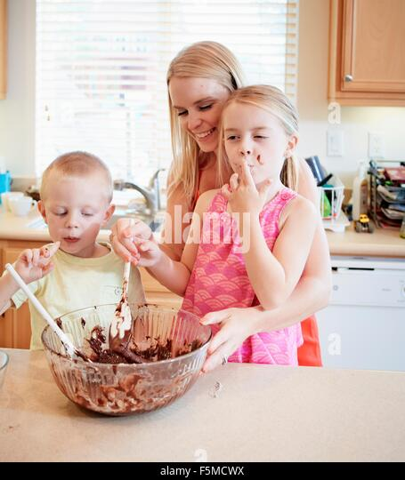 Family melting chocolate in mixing bowl - Stock Image