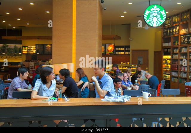 Singapore Raffles City Shopping Centre center shopping Starbucks Coffee cafe restaurant Asian man woman customers - Stock Image