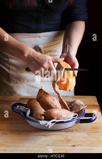 Female peeling orange sweet potatoes. - Stock Image