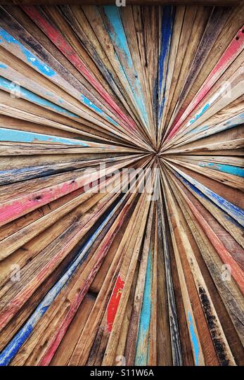 A colourful and abstract wooden background with lines converging off centre. - Stock Image
