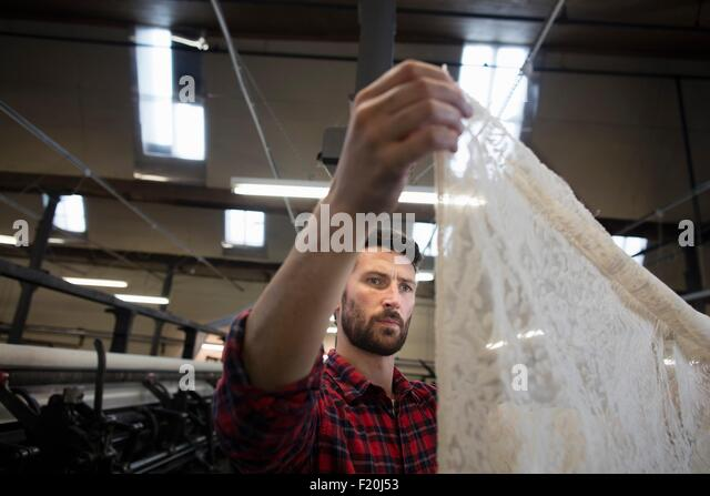 Portrait of male weaver examining lace cloth from old weaving machine in textile mill - Stock-Bilder