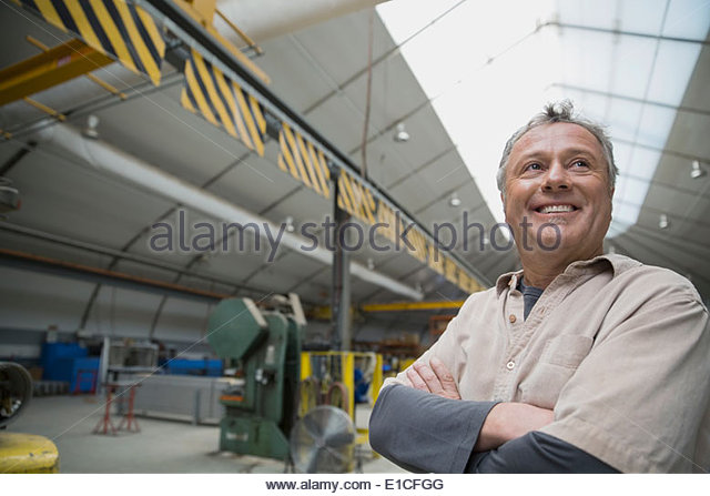 Smiling worker in manufacturing plant - Stock Image