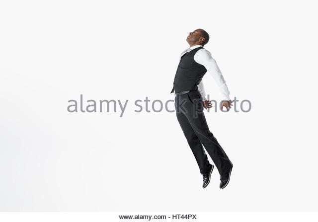 Businessman jumping chest forward against white background - Stock-Bilder