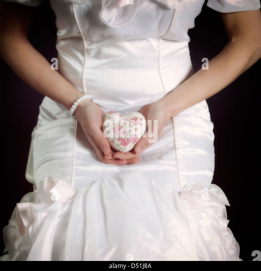 a woman in a white dress with a floral heart in her hands - Stock Image