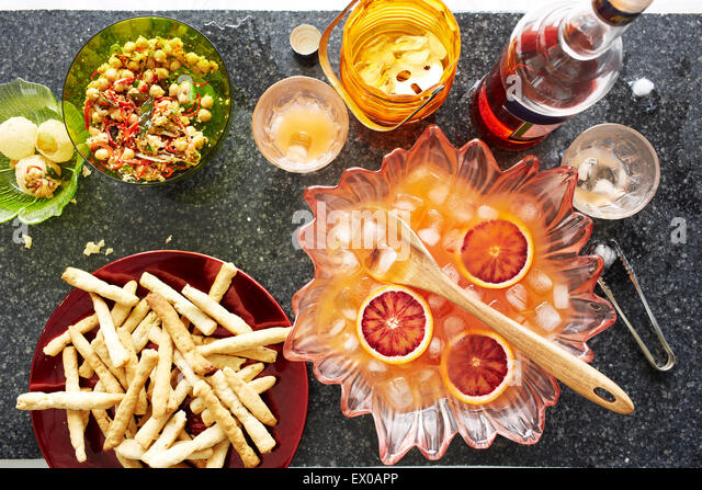Still life of punch cocktail bowl with crisps and snacks - Stock-Bilder