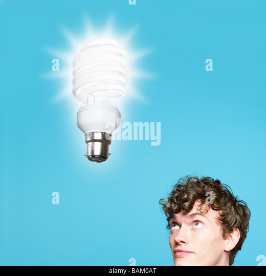 A young man looking at an energy saving lightbulb - Stock Image