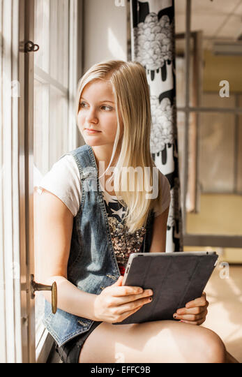 Girl holding tablet computer while looking through window at school - Stock Image