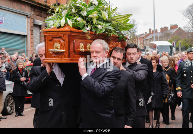 Martin McGuinness carries a coffin at a Funeral. - Stock Image