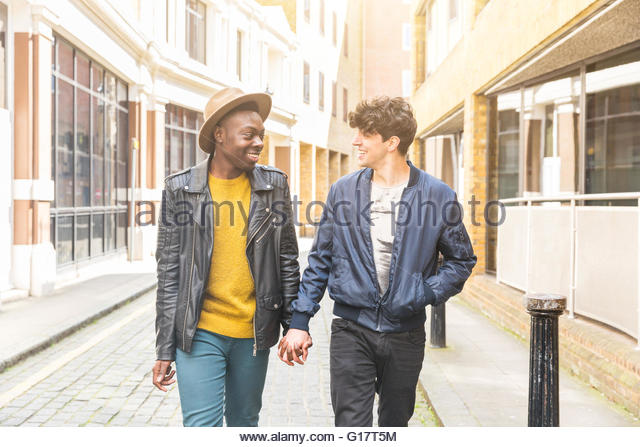 Homosexual couple in street, holding hands face to face smiling - Stock-Bilder