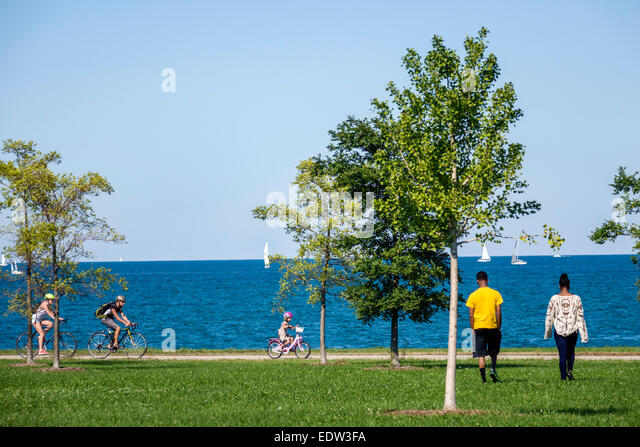 Chicago Illinois South Side Lake Michigan 39th Street Beach Lakefront Trail water trees biker riding bicycle rider - Stock Image