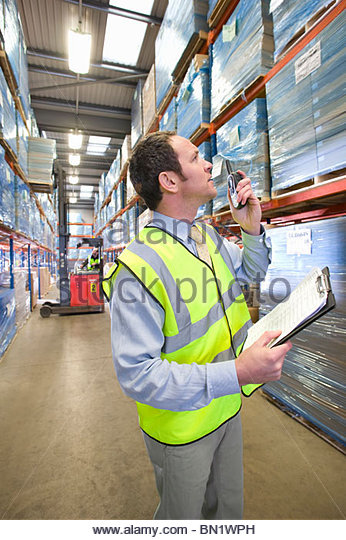 Warehouse manager holding clipboard and using walkie-talkie - Stock Image