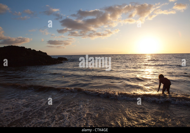 child reaching down to touch the ocean wave at sunset, Maui. - Stock Image