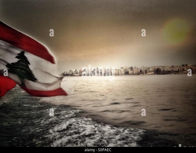 Water ,sea ,Beirut,lebanon,flag,red,green,white,Lebanese flag,sunrise,clouds - Stock Image