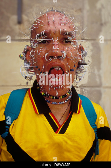 Man with multiple rings and spikes piercing his face, head, tongue, and ears, Havana, Cuba - Stock Image