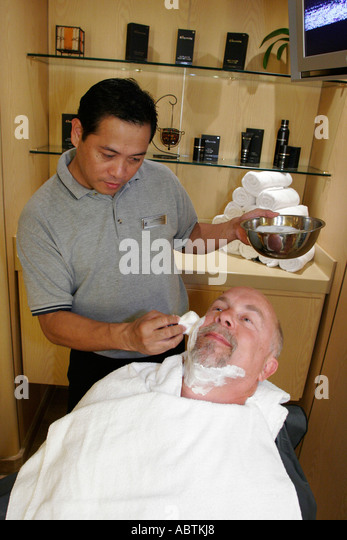 Puerto Rico Atlantic Ocean Holland America Line ms Noordam Greenhouse Salon Asian male shaves White man cream - Stock Image