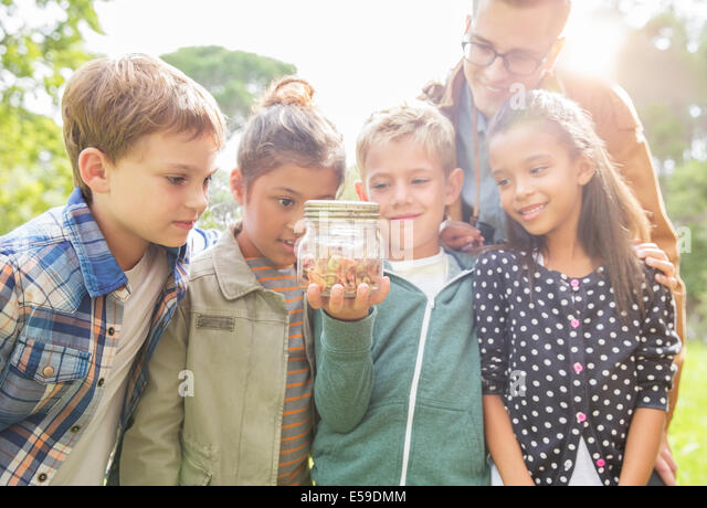 Student and teacher examining insects in jar outdoors - Stock Image