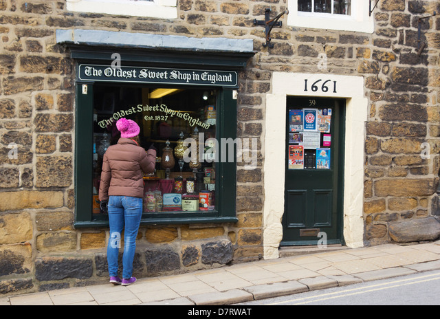 Pately Bridge, North Yorkshire, England. Girl looking in window of the Oldest Sweet Shop in England, founded in - Stock-Bilder