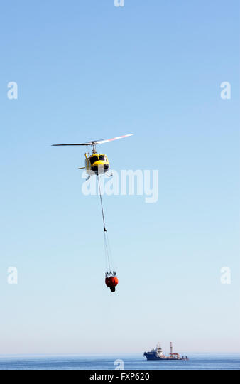One of Cape Town's 'Working on Fire' emergency aerial fire fighting helicopters with a water bucket - Stock Image