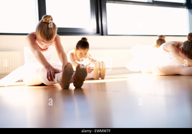 Little Ballet Girls Doing a Sit and Reach Warm-up Exercise for Body Stretching Inside the Studio, Prior to their - Stock Image
