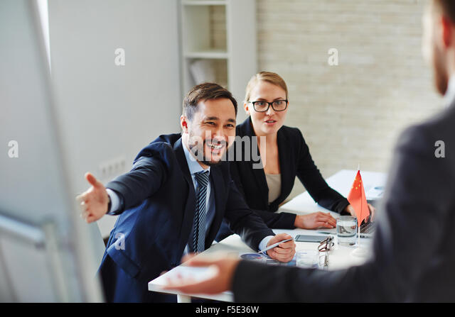 Business people welcoming and registrating foreign partners before conference - Stock Image