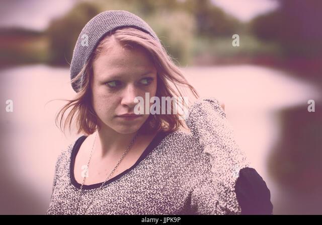 Vintage photo of sad teenager girl at autumn lake - Stock Image