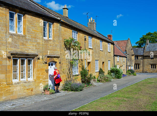 Postman delivering letters to cottages in the village of Montacute, Somerset, England UK - Stock Image
