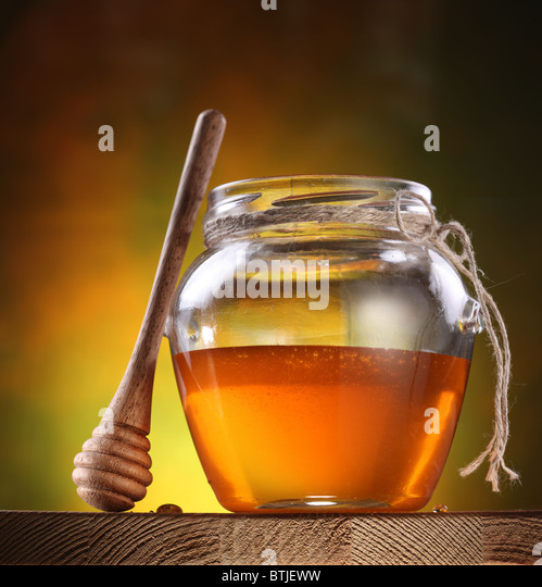 Pot of honey and wooden stick are on a table. - Stock Image
