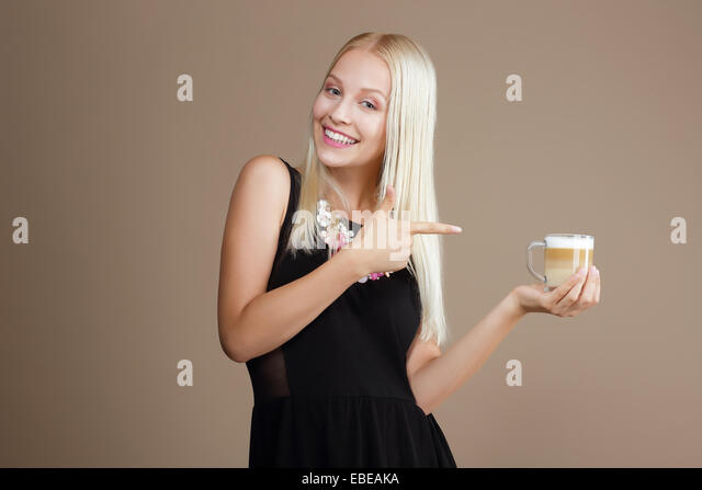 Happy Blond Woman Points Out to the Cup of Coffee - Stock Image