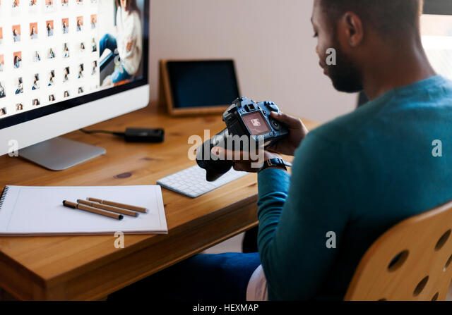Young photographer editing images at desk - Stock Image