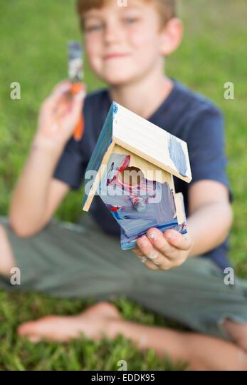 A boy in a garden, painting a bird house. - Stock Image