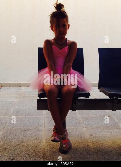 Small girl sitting alone - Stock Image