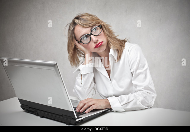 Bored blonde woman with glasses using a laptop - Stock-Bilder