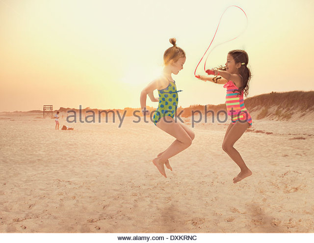 Girls jumping rope on beach - Stock Image