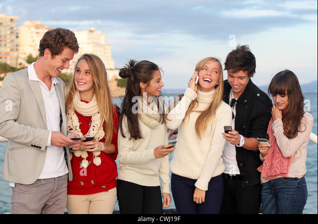 group of happy smiling teens, kids, texting and calling with mobile or cell phones. - Stock Image