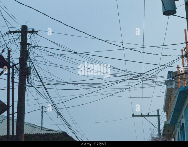 A jumble of electrical and telephone wires crisscross the sky in Totonicapan, Guatemala. - Stock Image