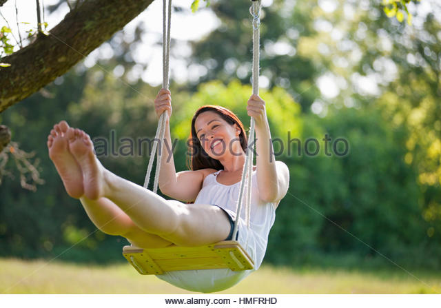 Happy barefoot woman swinging on tree swing in sunny summer, yard, carefree, fun - Stock-Bilder