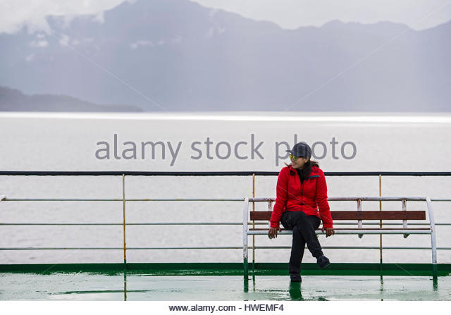 Woman sitting on ship-deck passing the Patagonian fjords, Chile - Stock-Bilder