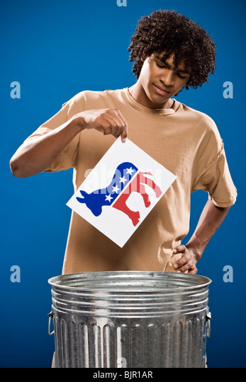 young man in a brown shirt throwing away a political party symbol. - Stock Image