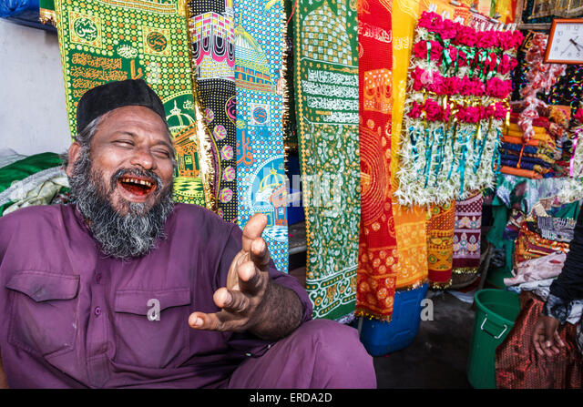 Mumbai India Asian Worli alley to Haji Ali Dargah mosque causeway sale man Muslim sidewalk vendor selling souvenirs - Stock Image