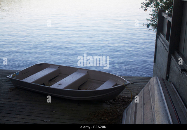 Row boats docked by a lake - Stock Image
