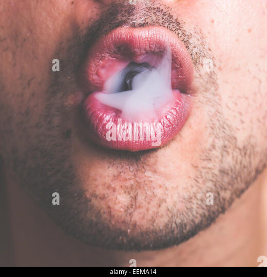 Cuba, Close-up shot of man's open mouth exhaling tobacco smoke - Stock Image