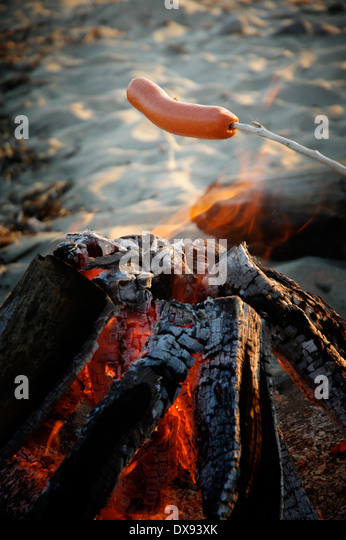Hot dog roasting over a beach fire. - Stock Image