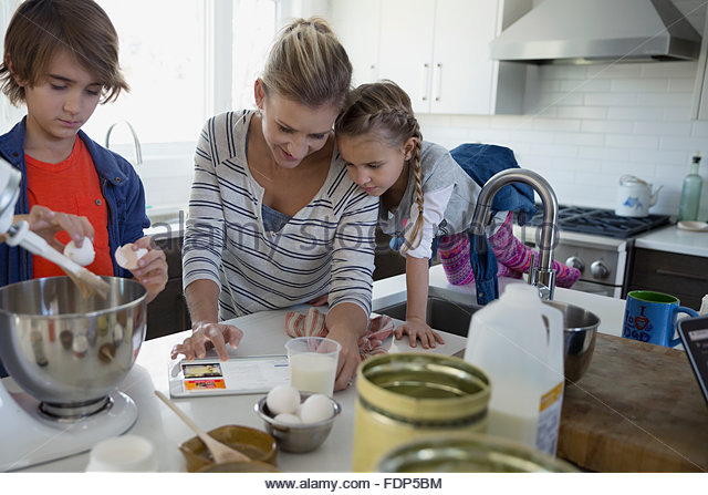 Mother and children baking with digital tablet kitchen - Stock Image