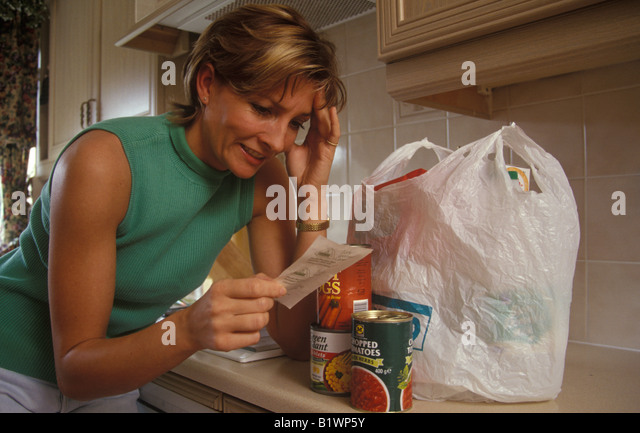 woman unpacking her shopping and looking distressed about prices - Stock Image
